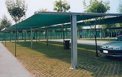 A car parks under green agriculture shade net