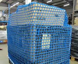 A blue cargo net covered goods on pallet at a factory