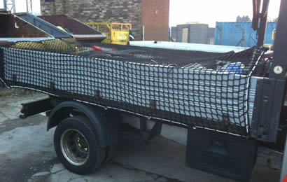 A black cargo net is covered on a trailer at the patio