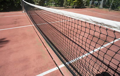 A piece black tennis net with white head band are installed outdoor